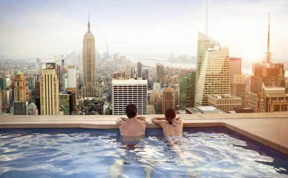 Couple relaxing in swimming pool on rooftop