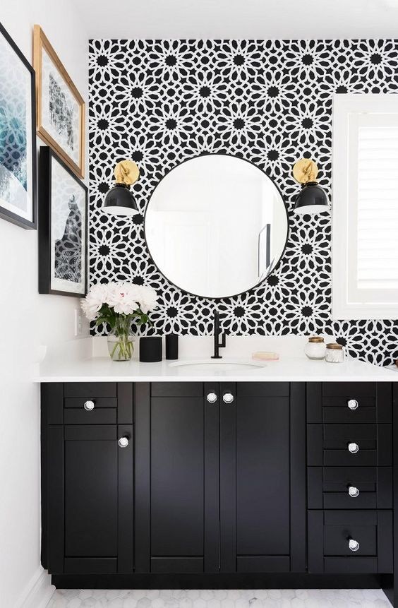Black and white pattern wallpaper in bathroom with round mirror, gold and black sconce lighting, and black vanity.: