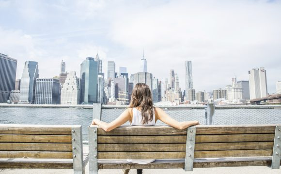 Woman sitting on a bench and looking at New York skyline - Tourist enjoys the view of Manhattan cityscape