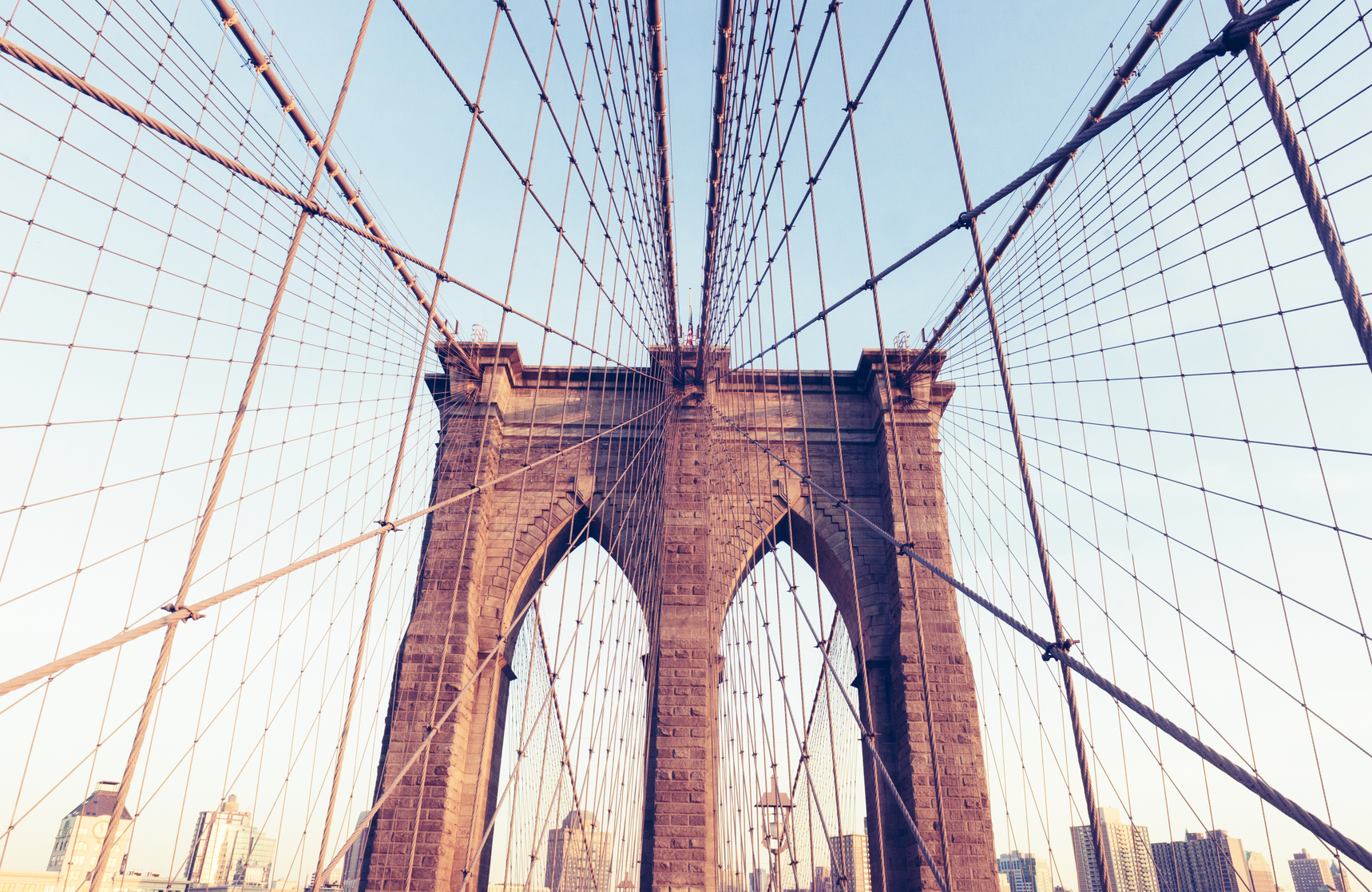 This is a color, horizontal, royalty free stock photograph of the famous, historic landmark, the Brooklyn Bridge in New York City. The iconic location connects the Borough of Brooklyn to the island of Manhattan. Suspension cables span out in all directions from the double arches.