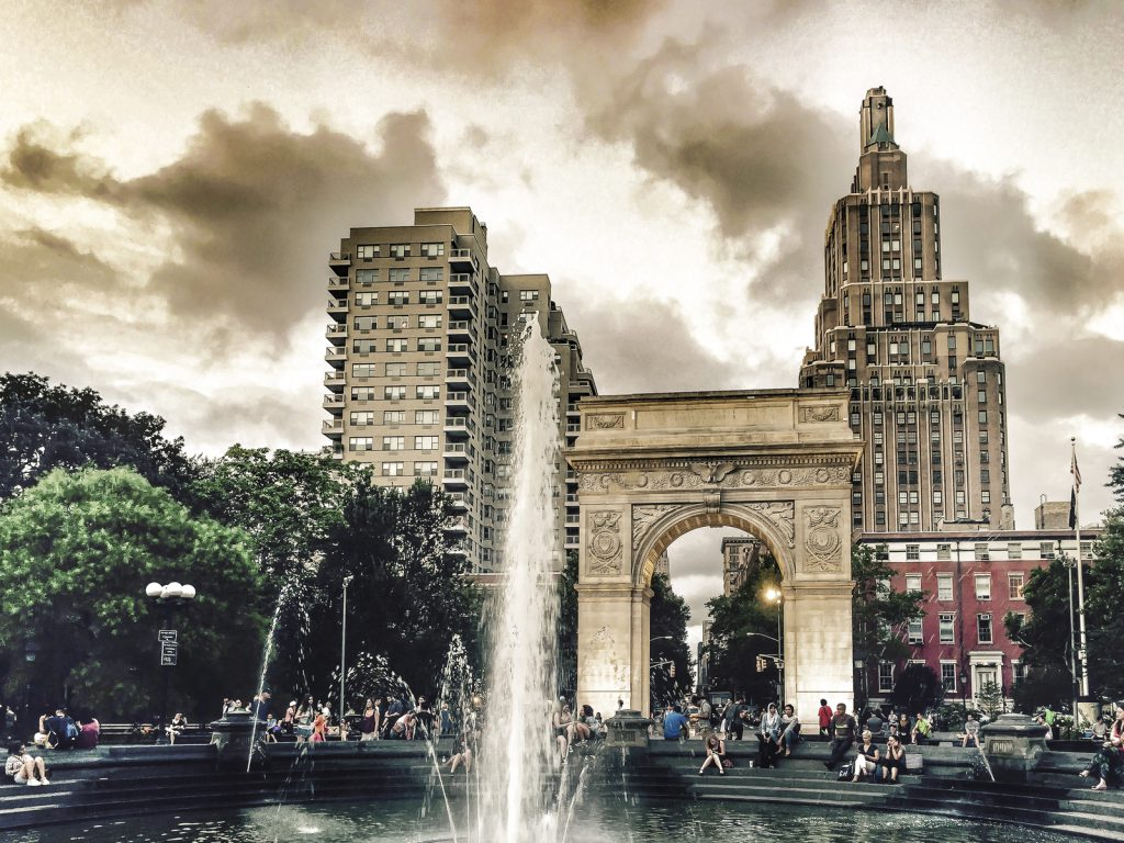 The beauty and vitality of Washington Square Park is heightened under a rare dramatic cloudy sunset in summertime.